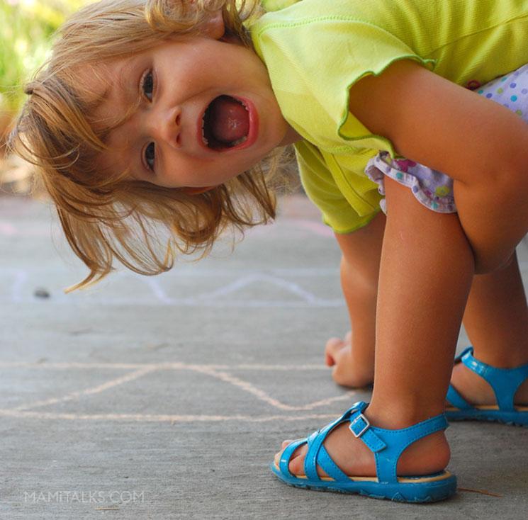 Little girl playing on sidewalk chalk game. -MamiTalks.com