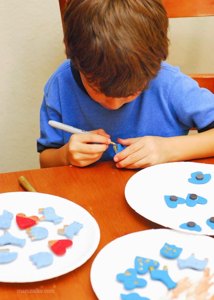 Niño pintando imanes de arcilla para San Valentín -MamiTalks.com