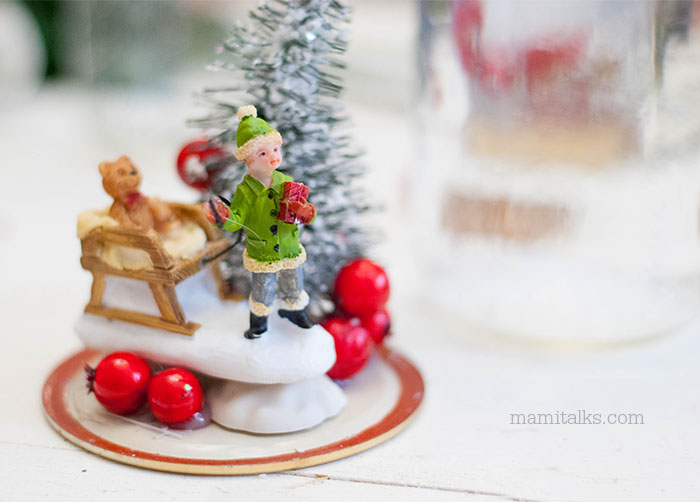 Making a snowglobe with jars, little boy pulling a sleigh with a background tree -MamiTalks.com