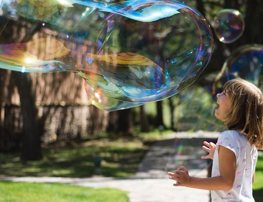 Girl playing with a giant bubble -MamiTalks.com