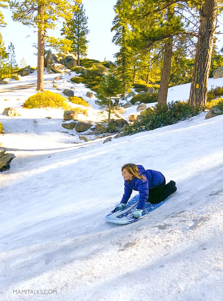 Little girl sledding down in Big Bear, CA. -MamiTalks.com