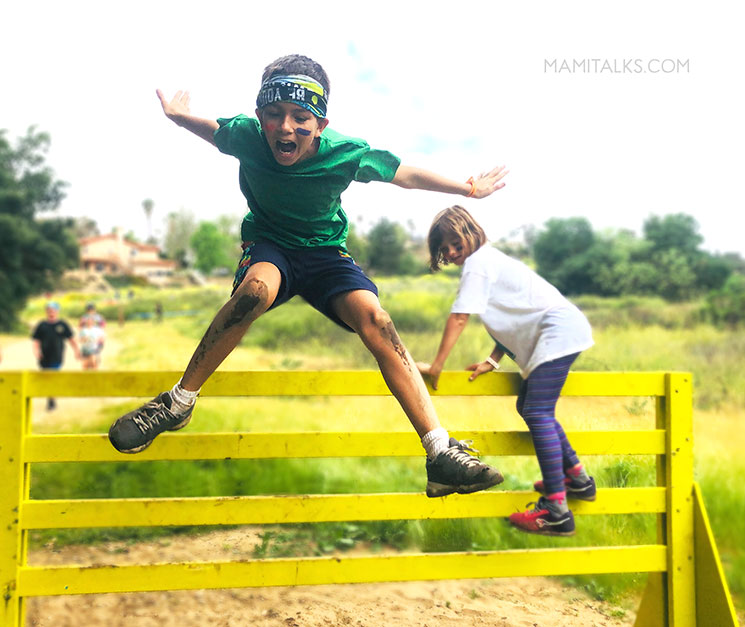 Kid jumping a big obstacle during a race. -MamiTalks.com