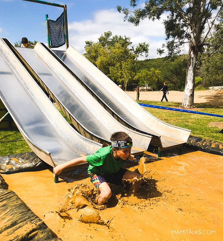 Kid sliding in mud. Mamitalks.com