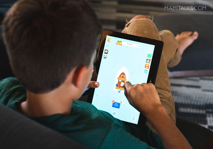 Kid playing games in tablet. Screen time controls. -MamiTalks.com