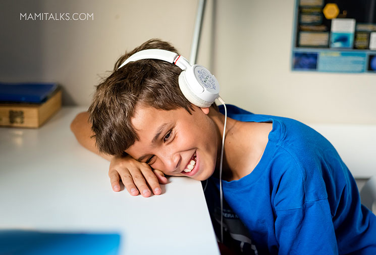 Boy laughing listening to a podcast with headphones. -MamiTalks.com