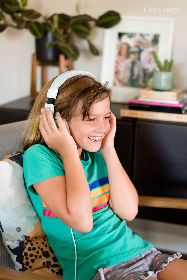 Niña escuchando podcast con audífonos. -MamiTalks.com