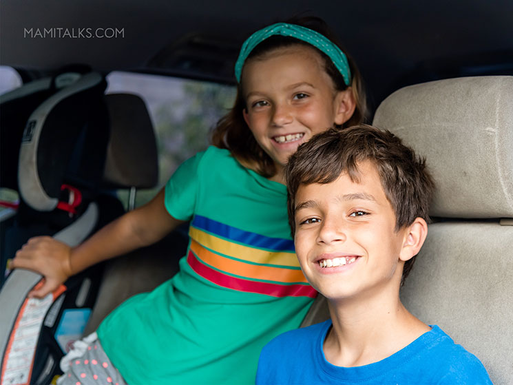 Niños en el carro sonriendo y escuchando podcasts. Favorite podcasts for tweens. -MamiTalks.com
