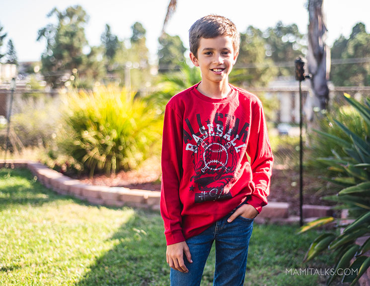 New way to shop kids clothes, boy standing in backyard, modeling a red sweater. MamiTalks.com