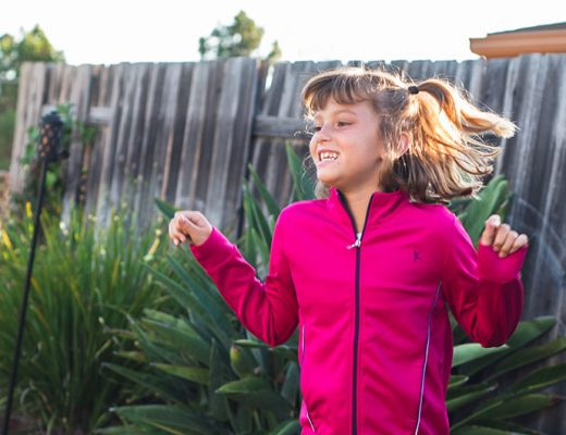 Girl jumping with pink jacket in backyard. Kids on 45th. A new way to shop for kid's clothes.