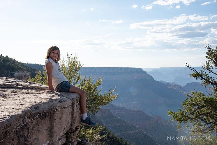 Girl sitting on the edge of the Grand Canyon. -MamiTalks.com