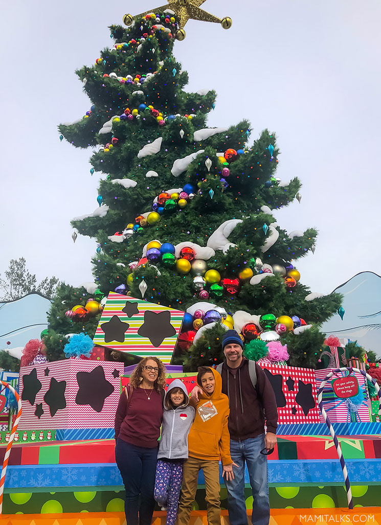 Holidays at Universal Studios Holywood, family in front of Grinchmas tree. -MamiTalks.com