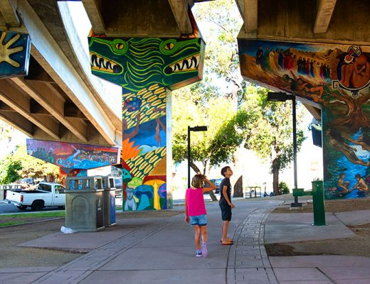 Kids looking at Chicano Park art under the freeway in San Diego. -MamiTalks.com